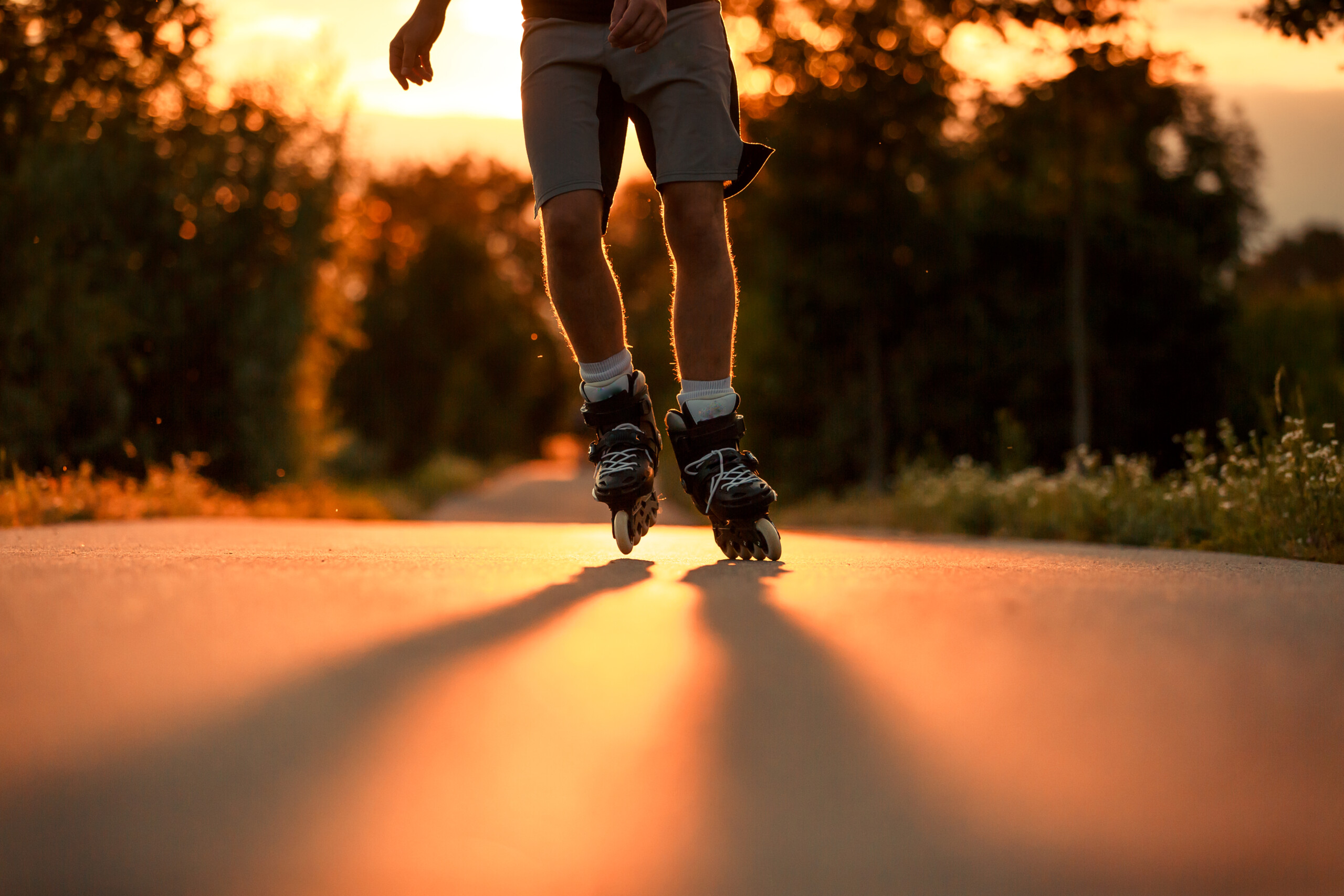 Young man on the roller skates during lovely summer sunset, sport concept, roller skating