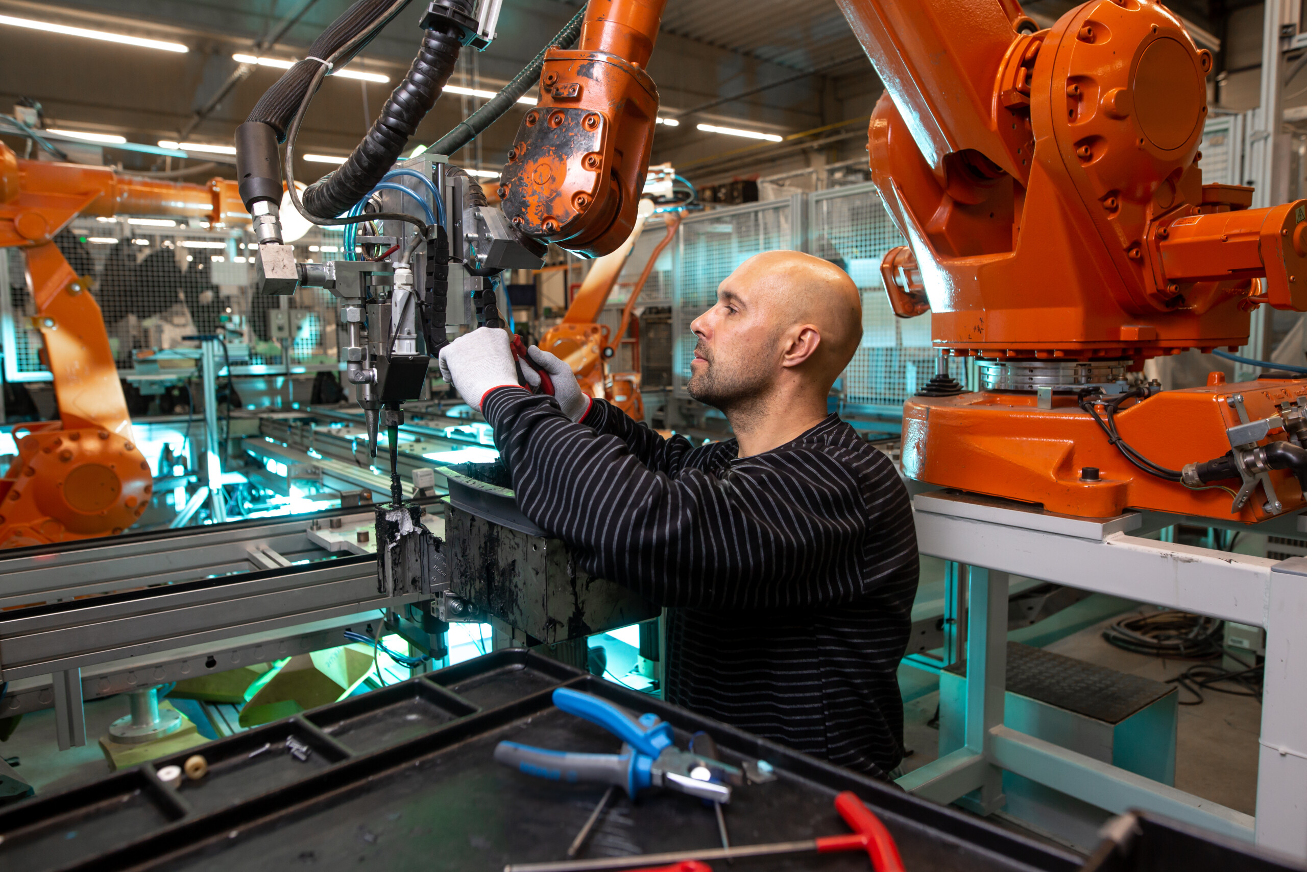 Engineer doing maintenance on a automatic robot arms in automotive industrial