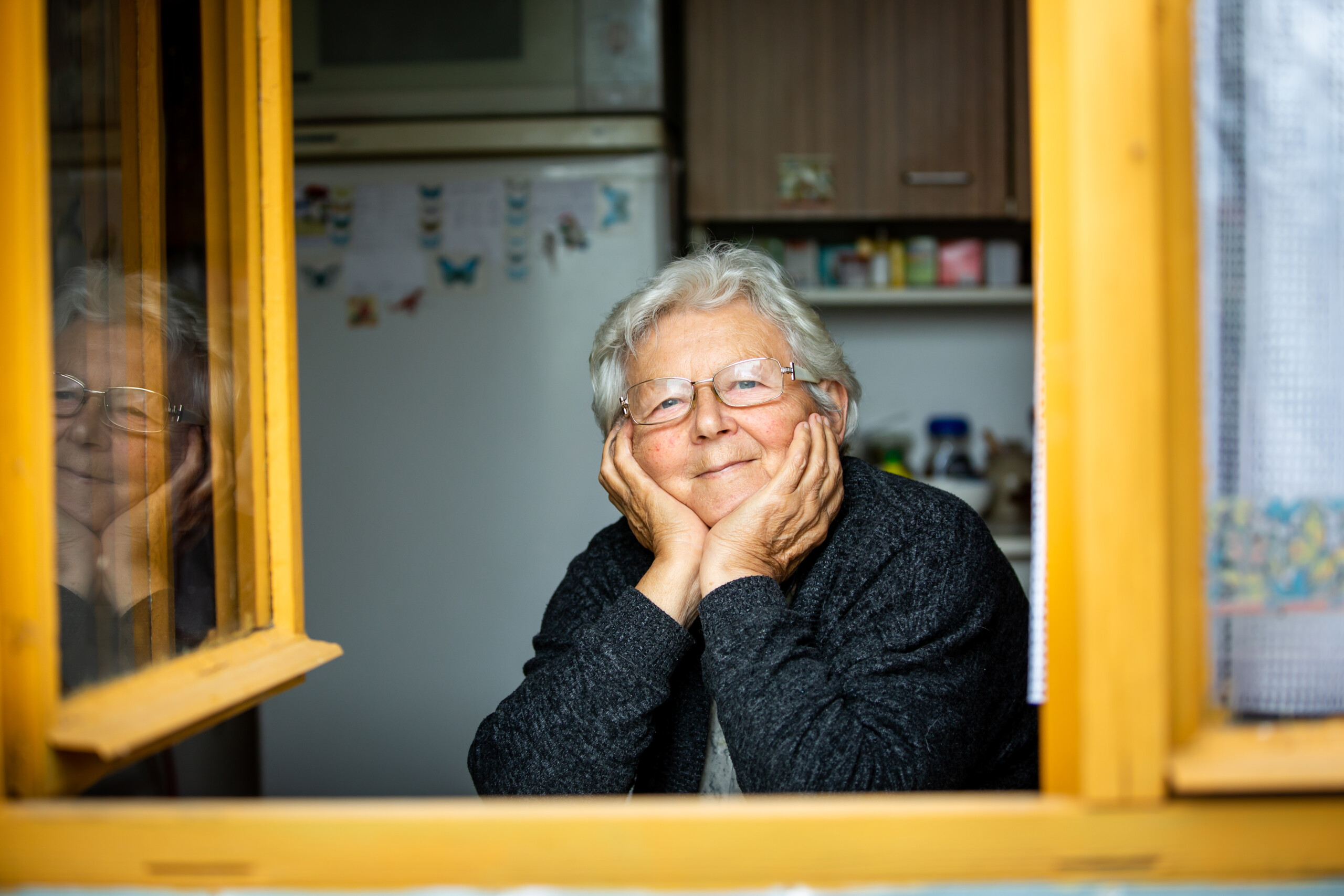 Portrait of lovely senior woman or grandmother watching out from a window and smiling, pensioner