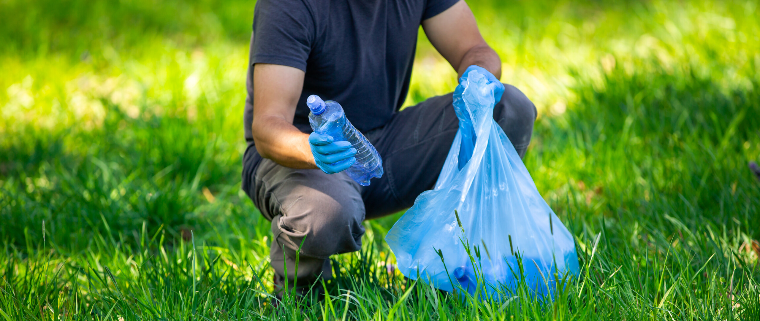 Man picking up plastic bottle, garbage collecting in forest cleaning planet, help garbage collection charity environment